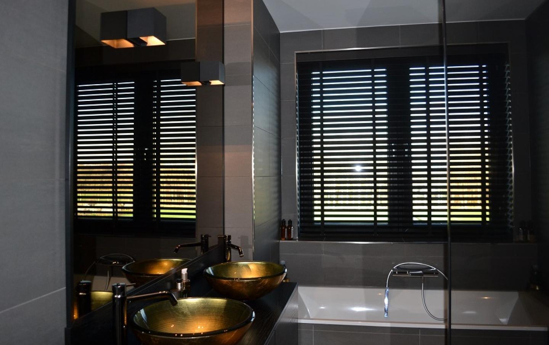 bronzen spiegel omkaderd met zwarte profielen, voorzien van verlichting